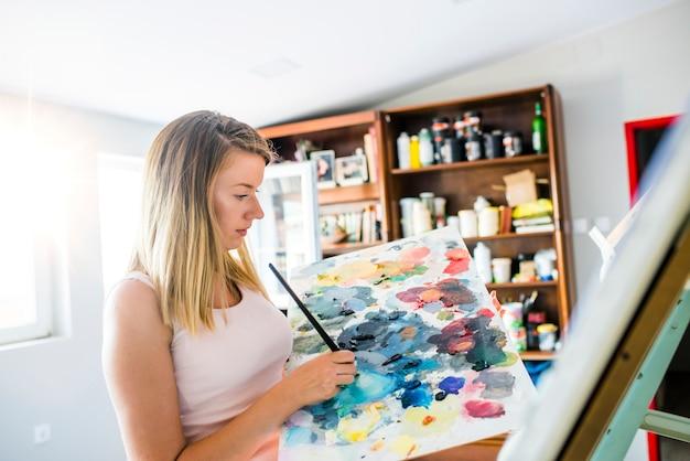 O artista pinta uma imagem da escova de pintura a óleo à disposição com a paleta.