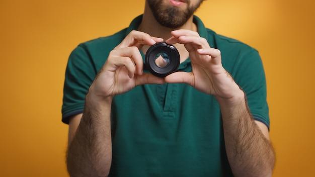 O artista visual gira o foco manual da lente enquanto grava uma resenha para o vlog. tecnologia de lente de câmera gravação digital influenciador de mídia social criador de conteúdo, estúdio profissional para podcast, vlogging