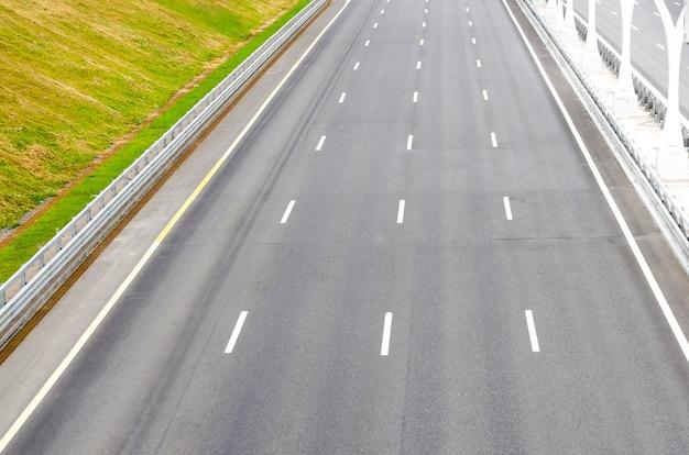 O asfalto de estrada de pista múltipla vazio deixa as marcações.