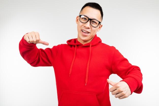 O asiático moreno bonito na camisola vermelha e nos óculos para a visão mostra os dedos em uma camisola em um fundo branco