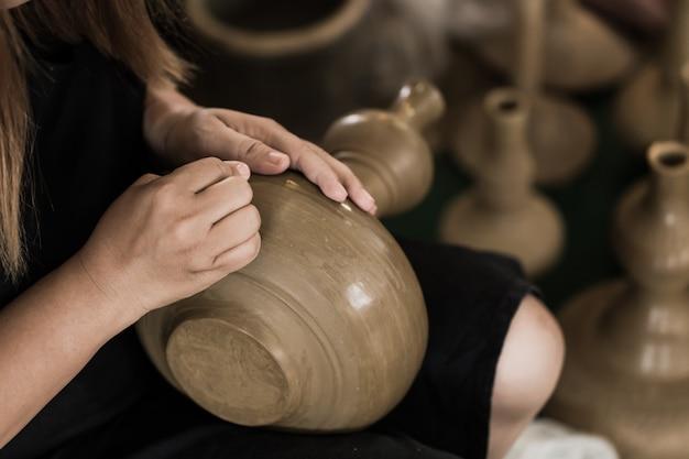 O asiático sênior handcraft o oleiro que faz o earthware do potenciômetro de argila à mão.
