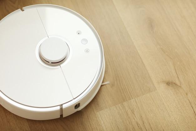 O aspirador de pó robô branco limpa o chão de detritos, limpeza doméstica com um aspirador elétrico, tecnologia de limpeza de robô aspirador de pó elétrico, vista superior de um aspirador de pó robô.