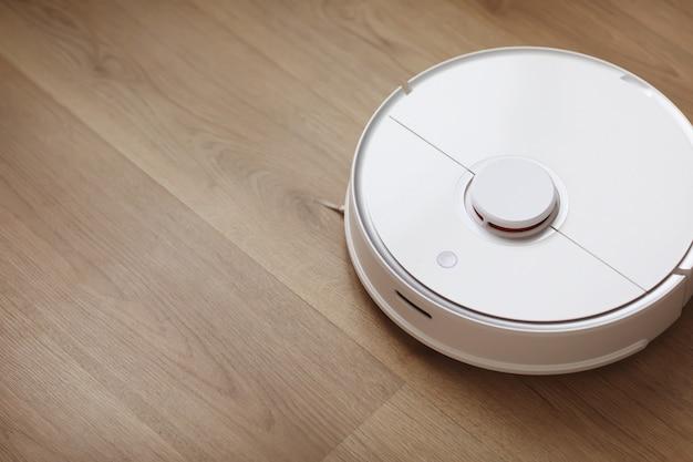 O aspirador de pó robô executa a limpeza automática do apartamento em um determinado momento. aspirador de pó robô branco. limpeza doméstica. lar inteligente. foco seletivo