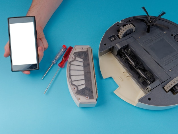 O aspirador robô é desmontado, o conceito de consertar um aspirador robô