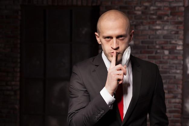 O assassino silencioso explora o conceito oriental das artes marciais. assassino careca de terno e gravata vermelha segura uma faca de combate. f