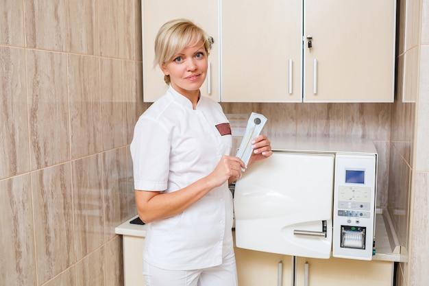 O assistente de dentista retira o instrumento desinfetado do esterilizador. instrumento odontológico esterilizado