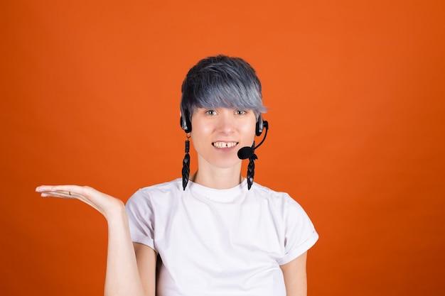 O assistente do call center com fones de ouvido na parede laranja parece feliz e positivo com um sorriso confiante segurando a mão com um espaço vazio à esquerda