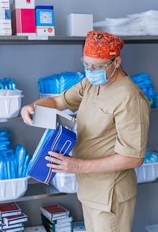 O assistente escolhe equipamentos e materiais adicionais para operação. armário de armazenamento. arrecadação. material para operação.