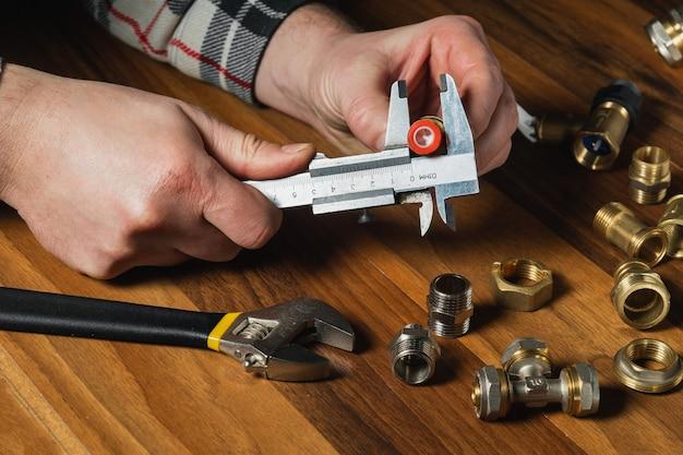 O assistente mede o tamanho da conexão usando um calibrador antes de conectar a tubulação de água ou gás