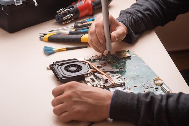O assistente restaura o laptop. desmontagem do laptop em peças sobressalentes. placa, parte do laptop para recuperação. manutenção de equipamentos de informática utilizando ferramentas. vista do laptop dentro