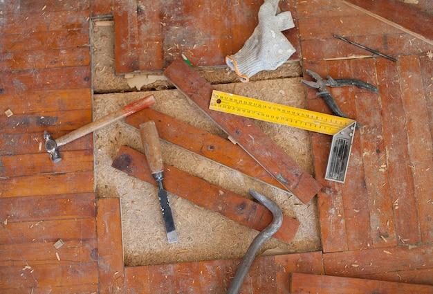 O assoalho de parquet podre velho remove com formão, ferramentas do martelo
