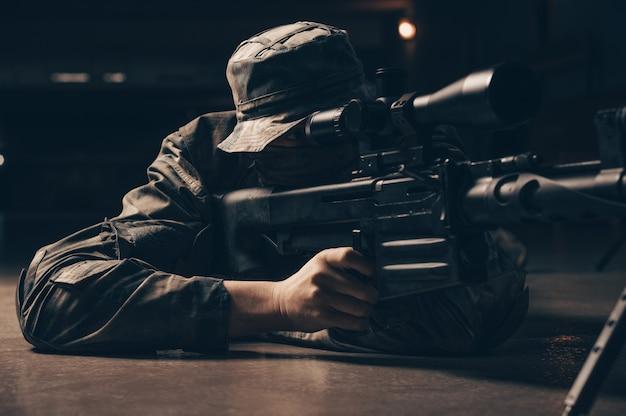 O atirador mente e mira através da mira telescópica. mídia mista