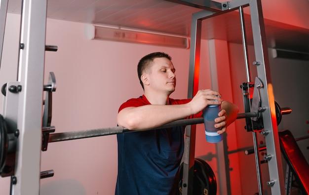 O atleta após o treinamento fica próximo à barra e segura um shaker com um shake de proteína. ginásio moderno de estilo de vida saudável.