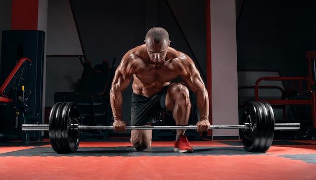 O atleta está de pé sobre o joelho e próximo à barra do ginásio e se prepara para fazer um levantamento terra.