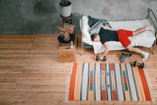 O atleta está descansando, descansando com halteres e adiando o treino em casa. o conceito de proastinação, preguiça esportiva