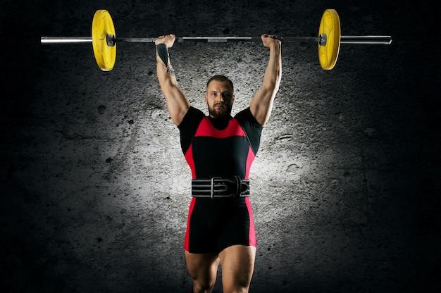 O atleta está em pé com uma barra acima da cabeça. vista frontal