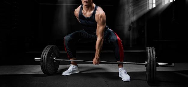 O atleta está em pé sobre o joelho e próximo à barra e se prepara para fazer um levantamento terra. mídia mista