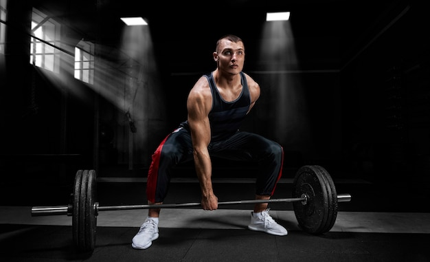 O atleta está em pé sobre o joelho e próximo à barra e se prepara para fazer um levantamento terra.