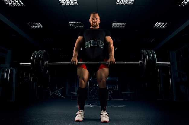 O atleta faz um levantamento terra. ele fixou a barra no topo e espera por uma contagem