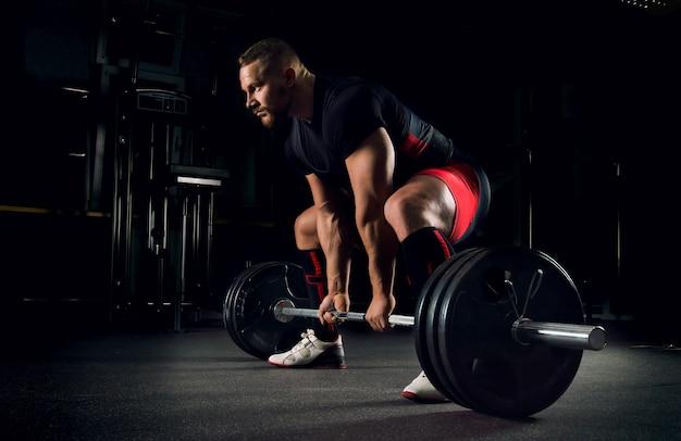 O atleta na academia está preparado para realizar um exercício chamado levantamento terra