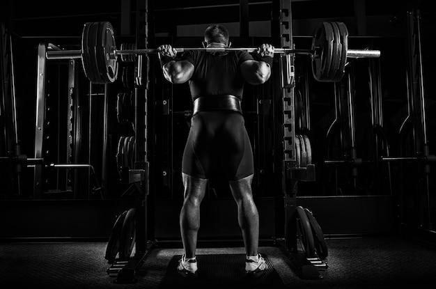 O atleta profissional está de pé com uma barra nos ombros e está prestes a sentar-se com ela. vista de trás.