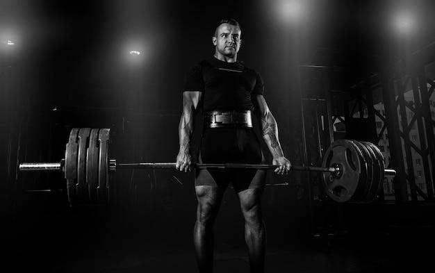 O atleta profissional está de pé e segurando uma barra muito pesada. vista frontal