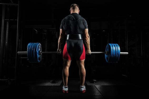 O atleta profissional está de pé e segurando uma barra muito pesada. vista traseira