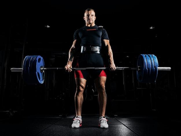 O atleta profissional está de pé e segurando uma barra muito pesada.