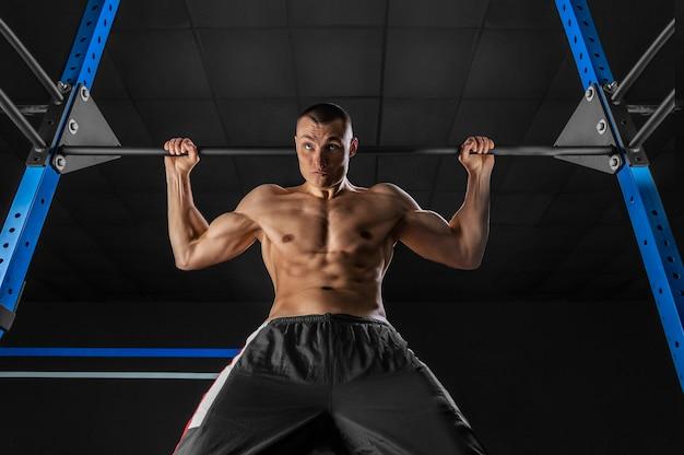 O atleta se posiciona na barra horizontal atrás da cabeça.