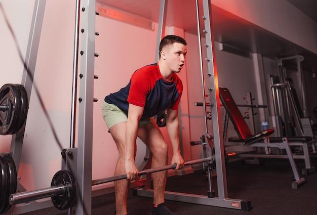 O atleta segura uma barra nas mãos enquanto se prepara para o agachamento. musculação na academia