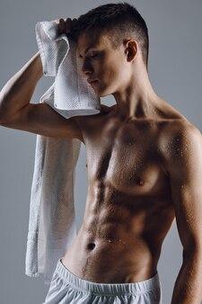 O atlético fisiculturista masculino bombeou toalhas de torso.