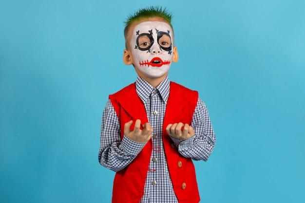 O ator assusta com os dedos. feliz dia das bruxas. menino de terno na parede azul com espaço livre.