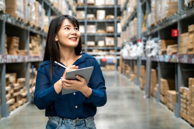 O auditor asiático novo da mulher ou o trabalho do pessoal do estagiário que olham acima e verificam o número de loja dos artigos pela tabuleta digital.