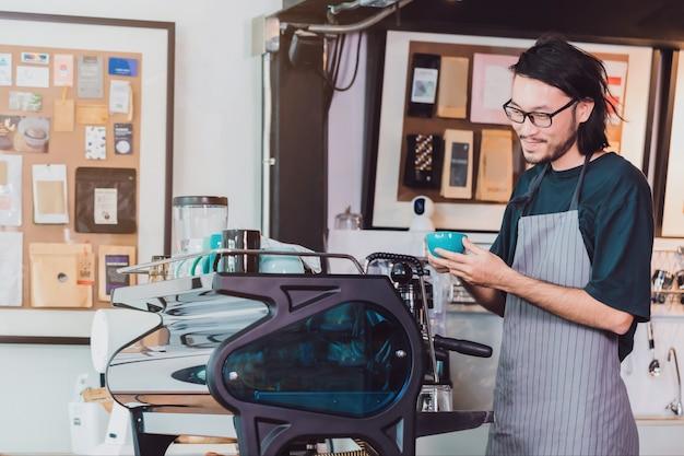 O avental asiático novo do desgaste do barista do homem que guarda o copo de café serviu ao cliente no contador da barra na cafetaria com cara do sorriso.