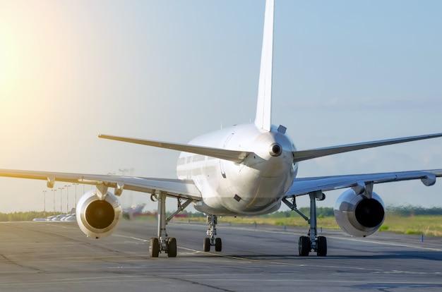 O avião branco dirige-se para o terminal no aeroporto após o pouso.