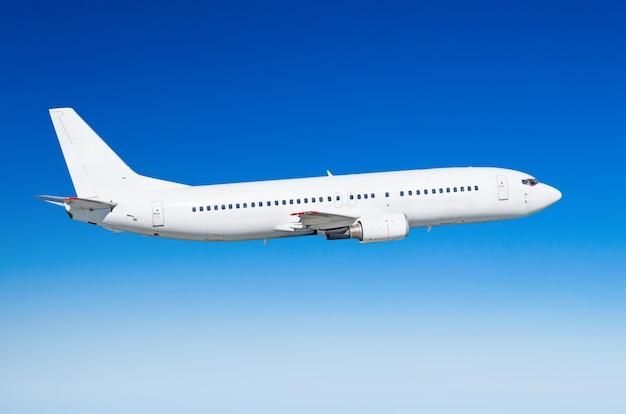 O avião branco do passageiro na vista lateral, voa em um céu nivelado do vôo.