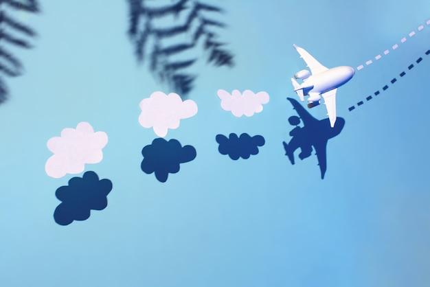 O avião branco está voando através do oceano. atrás dele estão nuvens e palmeiras.