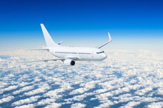 O avião branco voa alto no céu acima do céu azul das nuvens.
