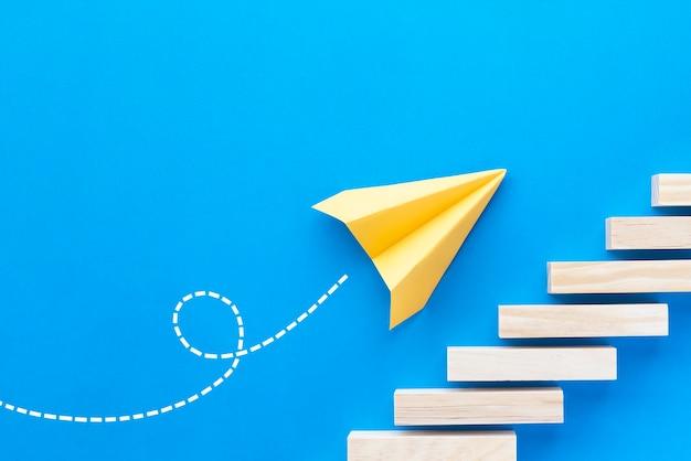 O avião de papel sobe as escadas. conceito de negócios