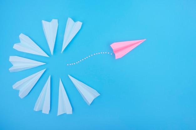 O avião de papel voa na direção oposta dos outros.