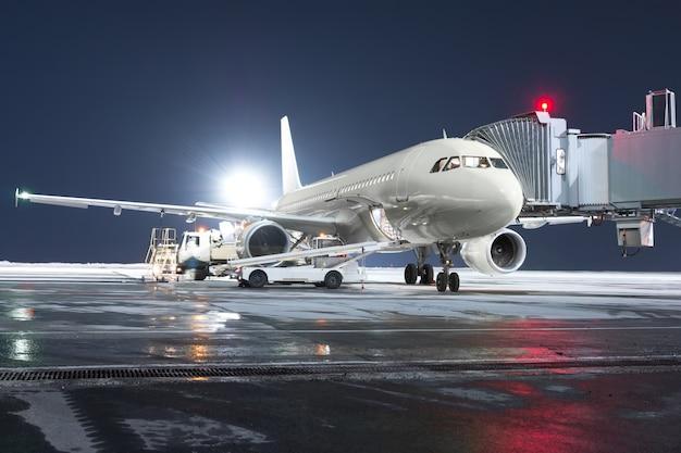 O avião de passageiros está parado na ponte de embarque no pátio noturno do aeroporto