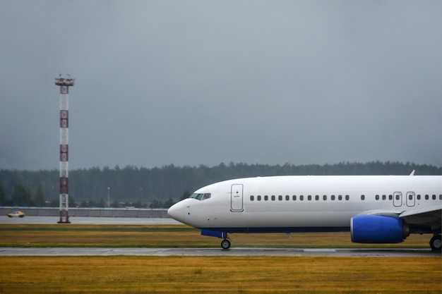 O avião de passageiros pousou na pista do aeroporto em mau tempo com chuva
