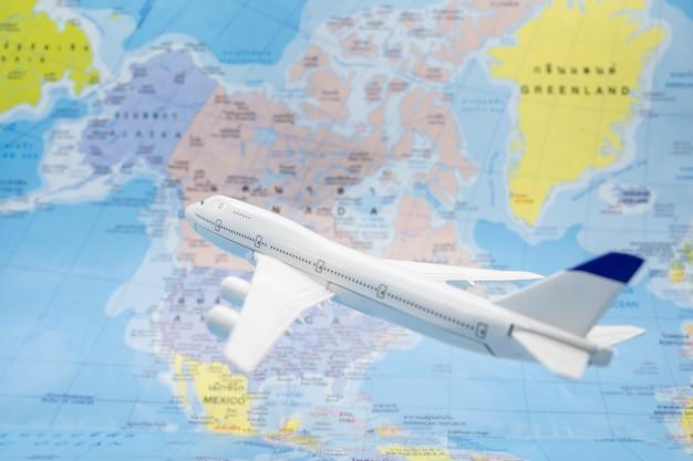 O avião do jato do brinquedo voa sobre no mapa do mundo colorido.
