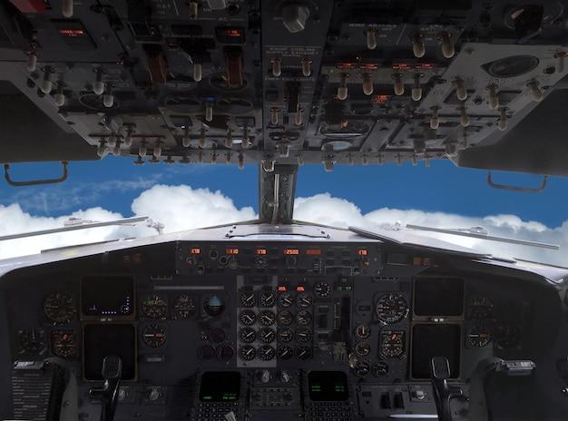O avião está voando sobre nuvens brancas no céu azul, vista do horizonte à frente da cabine do piloto