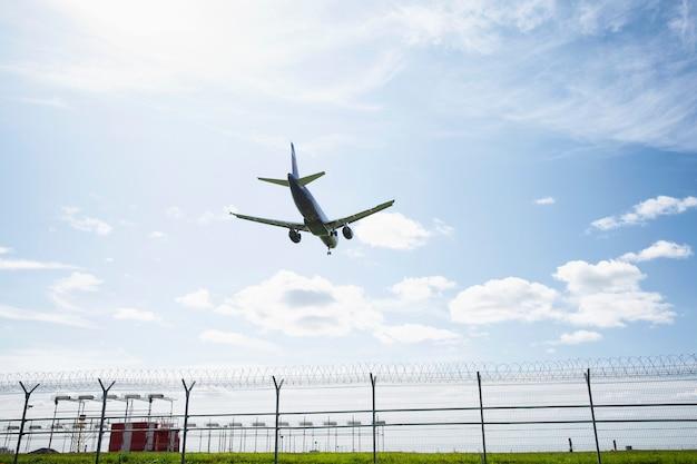 O avião pousa na pista do aeroporto contra um céu azul brilhante.