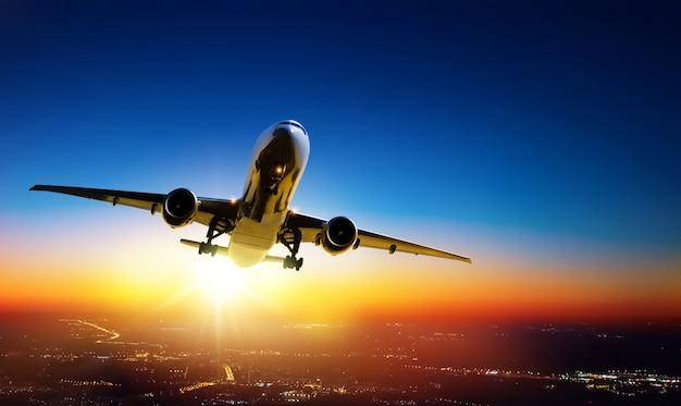 O avião vai decolar ao pôr do sol sobre as luzes da cidade