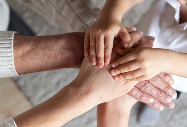 O avô, a filha e o neto juntos formam uma pilha de palmas e mãos. união familiar feliz. família feliz e apoio para o conceito de pais idosos. Foto Premium