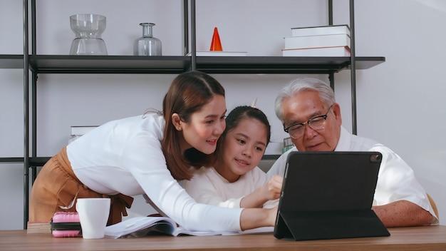 O avô e a mãe estão ensinando lição de casa para a filha enquanto estudam online em casa.