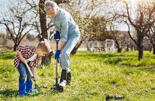 O avô e o neto, ambos usando botas de borracha, aproveitando os dias de primavera, enquanto trabalham no jardim e cavam um buraco no chão
