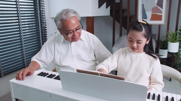 O avô está ensinando a neta a tocar piano em casa.